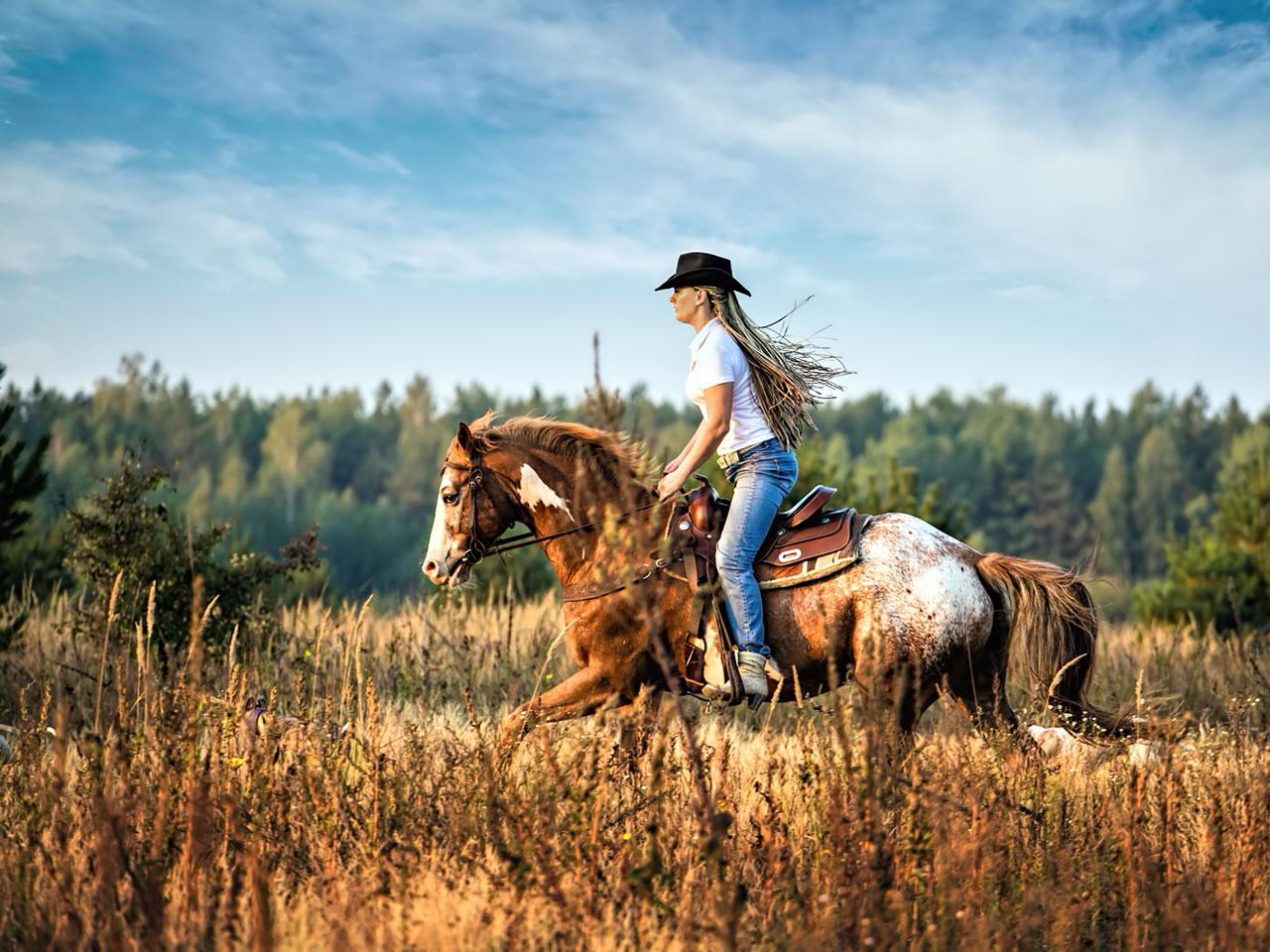 Frau reitet auf einem Appaloosa